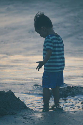 Boy Standing On Shore At Beach Against Sky