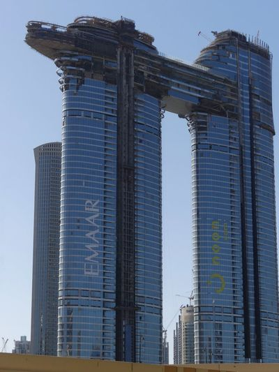 Two Tower Skyscrapers being joined together by a ship shape top under construction on Sheik Zayed Road, Dubai, United Arab Emirates 2019 Dubai UAE 2019 Sheik Zayed Road Blue Sky Under Construction Two Skyscrapers Two Towers No People Low Angle View Tall - High Emaar Ship Shape Modern Architecture Modern Design Glass And Steel Structures City Full Frame Composition Outdoor Photography Sunlight And Shade Modern Travel Destinations Unusual Shape Building Facade