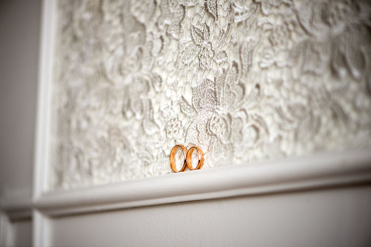 Wedding rings on white lace, marriage accessory, engagement background