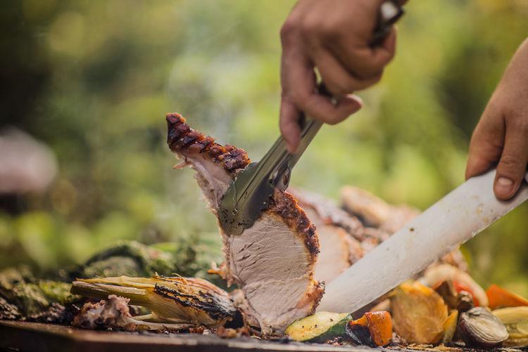 Slicing roasted pork in summer garden