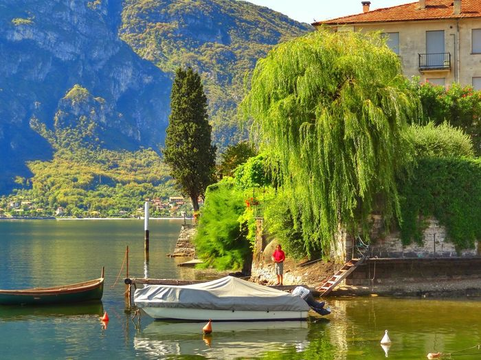 Man standing on jetty by boat moored in lake como
