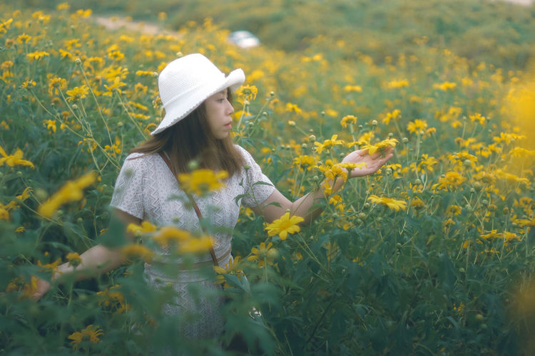 Woman with yellow flowers on field