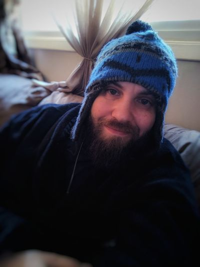 Portrait of smiling beard man with knit hat sitting on sofa at home
