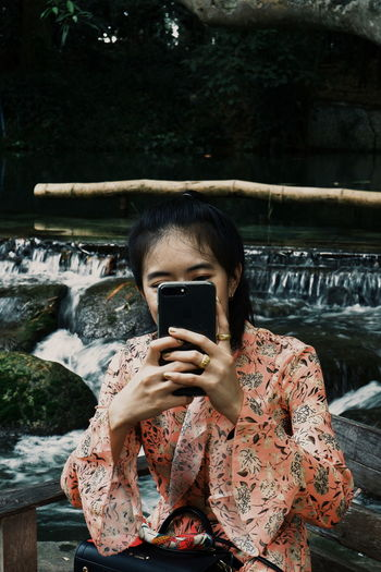 Close-up of woman taking selfie against waterfall