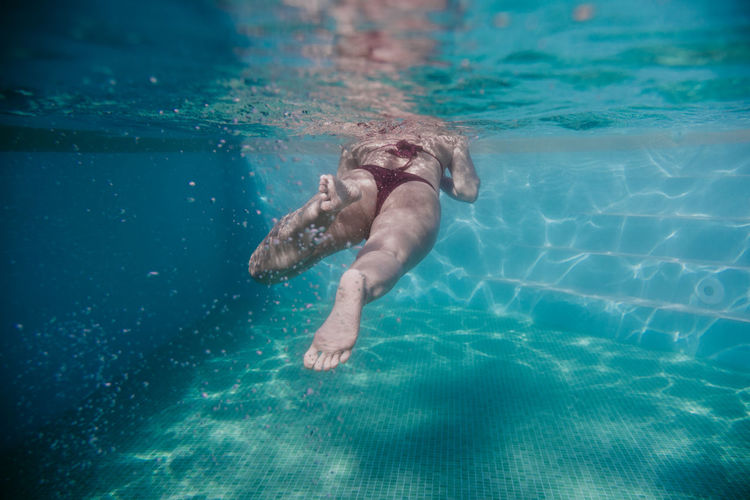 Mid adult woman swimming underwater in pool