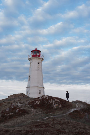 Low angle view of man by lighthouse against sky
