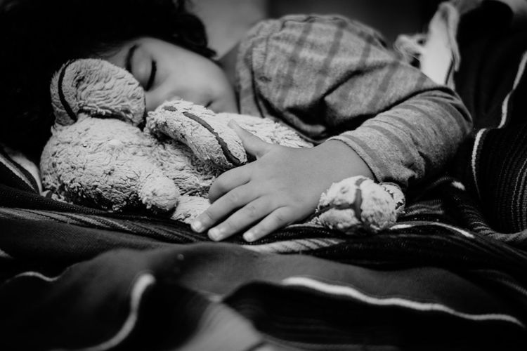 Close-up of girl with toy sleeping on bed at home