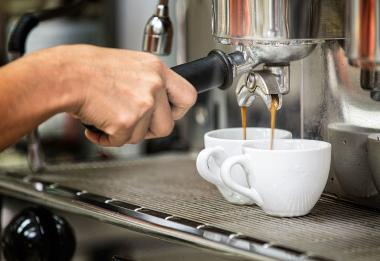 Cropped hand of worker pouring coffee into cups at cafe