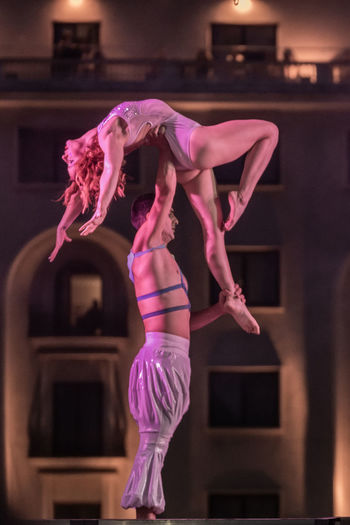 Midsection of woman dancing against pink indoors