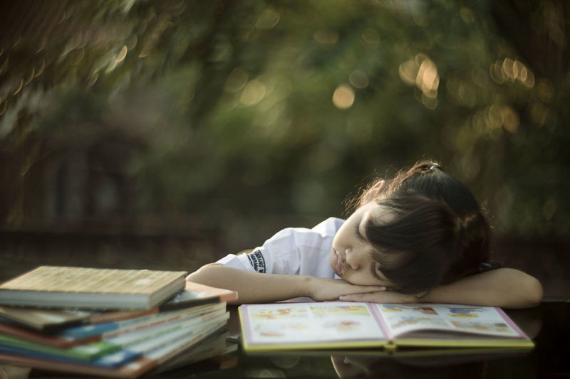 A little girl studying wearing a school uniform at the outdoor class with glimmering background in the morning light Book Childhood Day Education Headshot Indoors  Learning One Person People Real People Sitting Studying