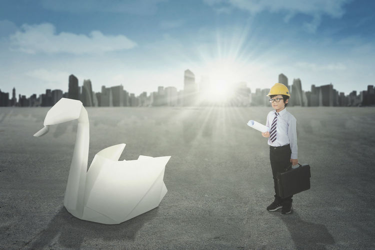 Digital composite image of boy with suitcase standing on road against sky in city during sunny day