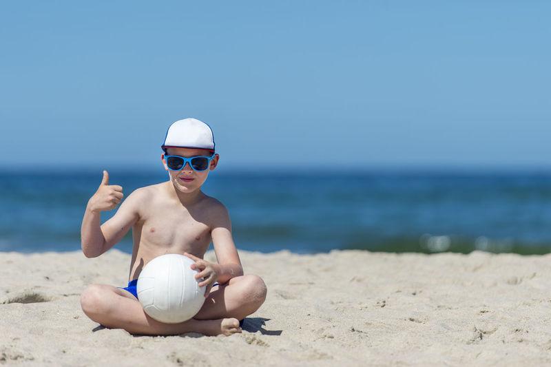 Full length portrait of shirtless boy on beach