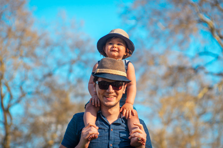 Portrait Of Happy Father Carrying Son On Shoulders Against Trees