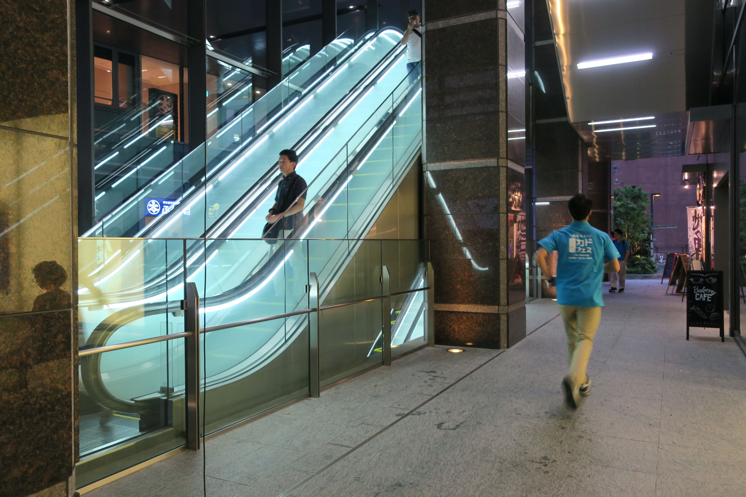full length, architecture, walking, men, built structure, rear view, railing, city, illuminated, front view, well-dressed, person, footbridge, engineering, city life, subway station, modern