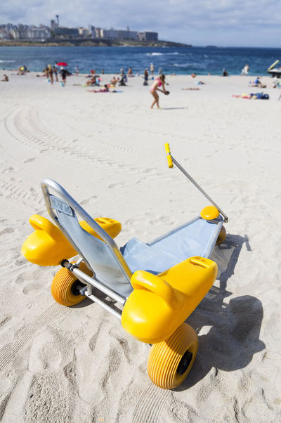wheelchair designed specifically for what disabled people can access the beach and bathing in the sea Aid Beach Coastline Disabled Disabled Person Incidental People Sand Social Assistance Tourism Vacations Wheelchair Wheelchair Design Yellow