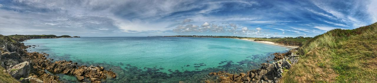 Panoramic view of bay against cloudy sky during sunny day