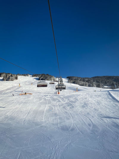Ski lift over snow covered field against clear blue sky
