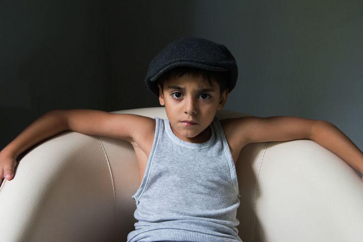 Portrait of boy wearing hat sitting against wall