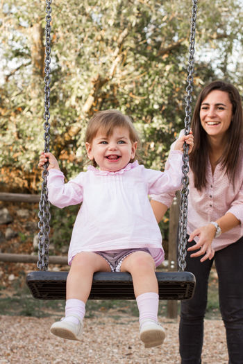 Smiling mother looking at daughter while swinging in playground