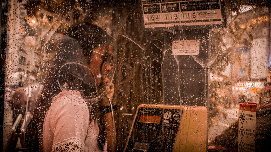 Teenage girl talking in wet telephone booth during rain
