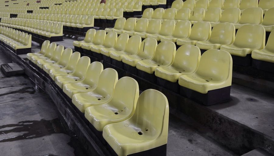 Yellow. In A Row Empty Indoors  Bleachers Repetition No People High Angle View Seat Large Group Of Objects Auditorium Stadium Day Solitude Symmetrical Symmetry Architecture_collection Architecture Sitting Black & White Yellow Yellow Color Neighborhood Map The Street Photographer - 2017 EyeEm Awards The Architect - 2017 EyeEm Awards The Great Outdoors - 2017 EyeEm Awards