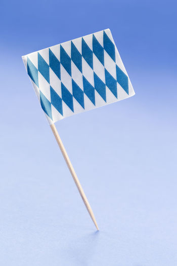 Close-Up Of Flag On Toothpick Against Blue Background