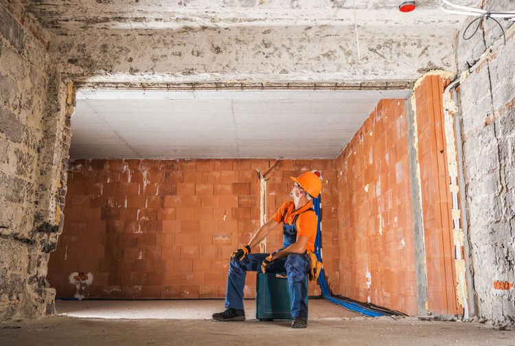 Full length of manual worker looking at ceiling