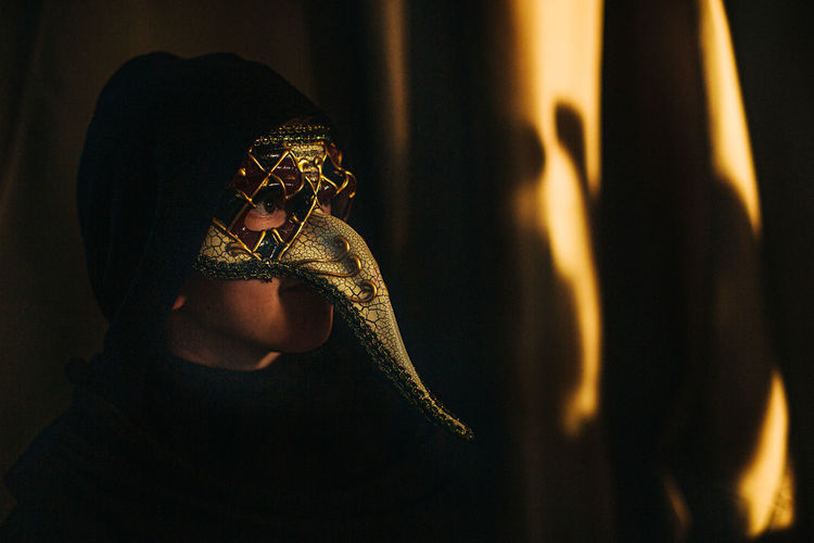 Close-up of boy wearing mask on stage