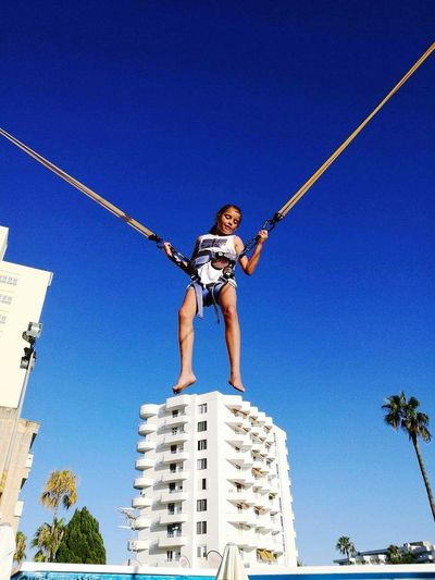 Maya at Majorca Skyscraper Clear Sky Low Angle View Business Finance And Industry City Blue Day Outdoors Sky Full Length Adult Urban Skyline People Tree One Man Only One Person Only Men Adults Only Trampoline Extremal Sport The Architect - 2017 EyeEm Awards Taking Photos Huwawei P9 Huwaei Photography Kids