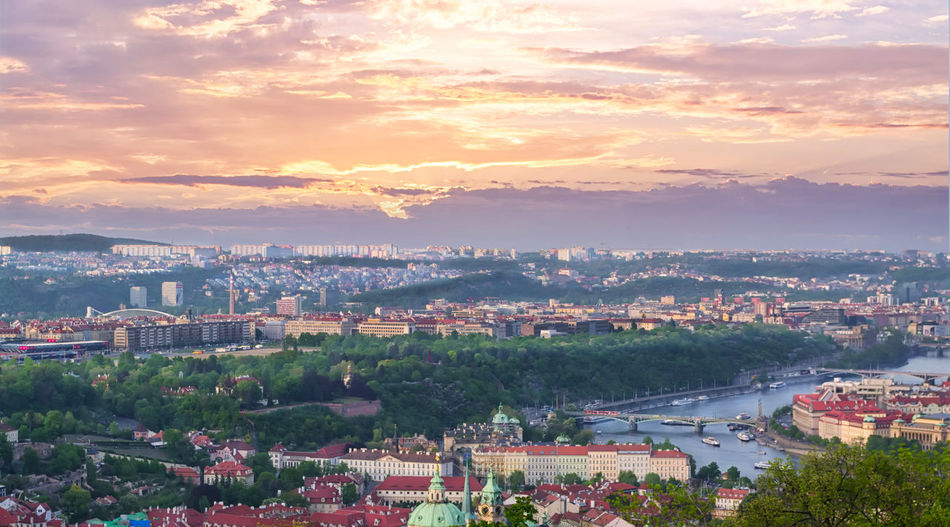 Beautiful high view of Prague and the Vltava river on a cloudy pink sky at sunset. European cityscape at twilight Bohemia Czech Republic Prague Praha Roof Scenic Top Twilight View Vltava Architecture Building Capital City Cityscape Clouds Evening Historic Landscape Outdoors River Sky Sunset Town Urban