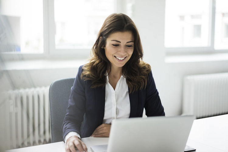 Young woman using phone while sitting in office