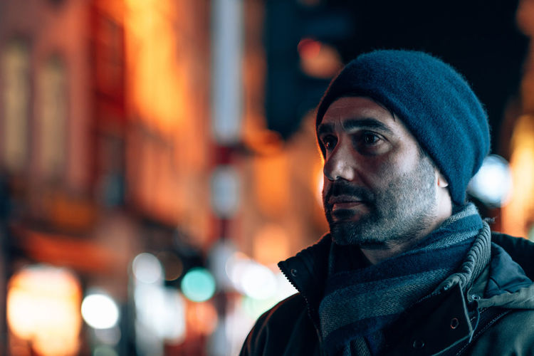 Portrait of a man in wool hat and scarf looking away with the city lights in background