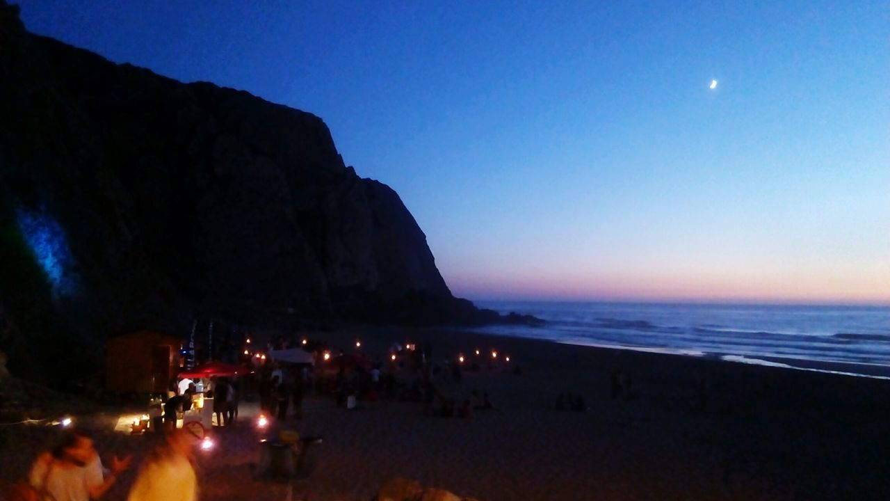 sea, nature, beauty in nature, scenics, beach, water, moon, night, sky, tranquility, tranquil scene, outdoors, clear sky, horizon over water, large group of people, leisure activity, vacations, real people, sand, blue, mountain, astronomy, people