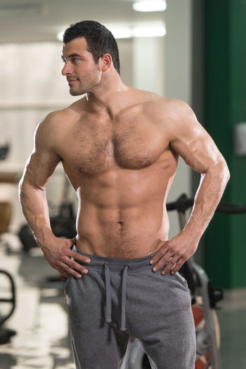 Shirtless Muscular Man With Hands On Hip Standing In Gym