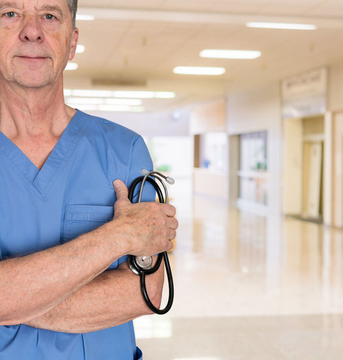 Senior male doctor or specialist welcoming patient to a hospital Doctor  Healthcare Hospital Man Medicine Surgeon Clinic Consultant Elderly Healthcare And Medicine Male Medical Occupation Old One Person Portrait Scrubs Senior Adult Specialist Stethoscope  Welcome