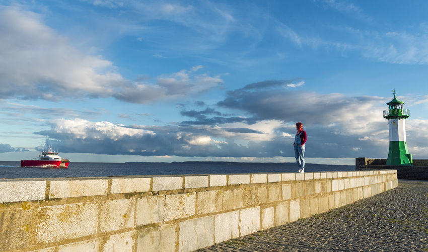 Man standing on retaining wall by sea against sky