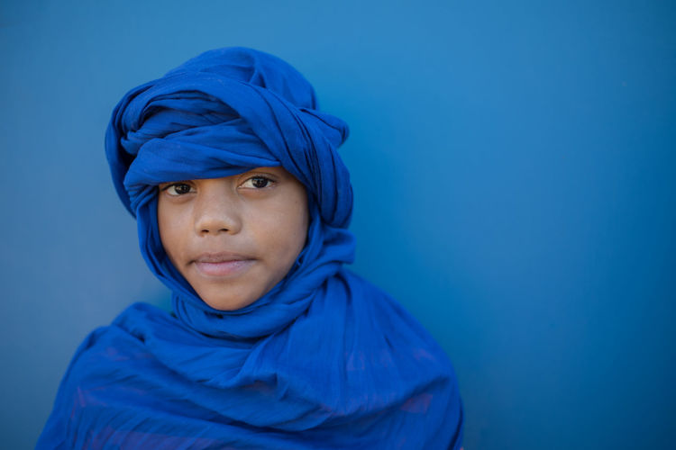 Close-Up Of Boy Wearing Fabric Against Blue Background