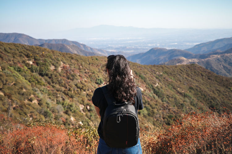 Rear view of woman standing on mountain landscape