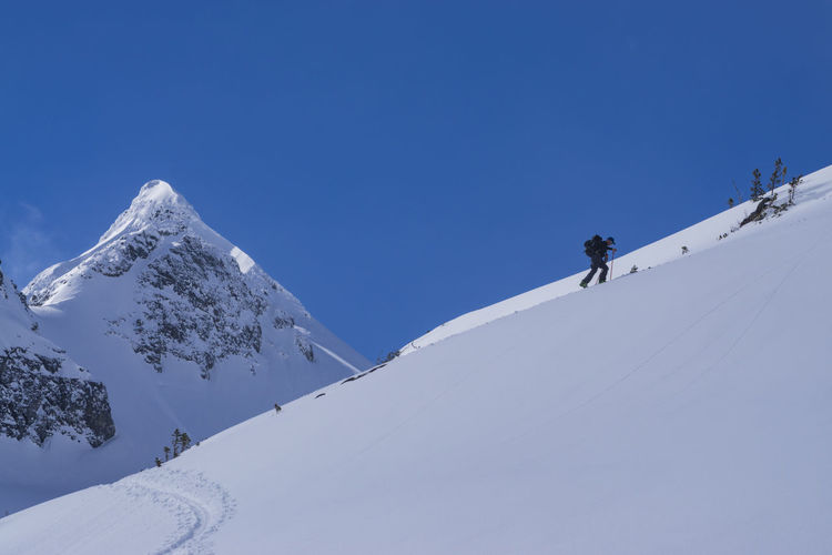 Low angle view of man climbing on snow covered mountain against blue sky