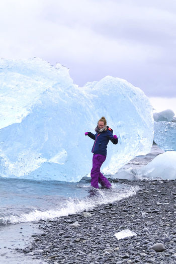 Full length of woman on sea against sky during winter