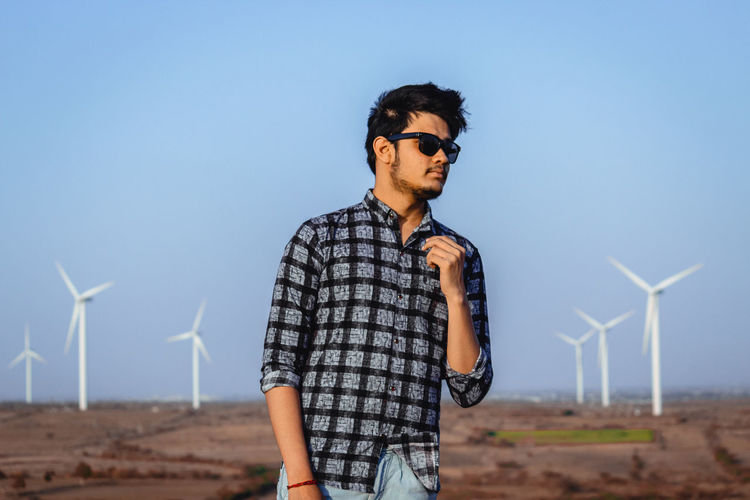 Renewable Energy Fuel And Power Generation Environment Sky Turbine One Person Alternative Energy Environmental Conservation Wind Turbine Young Adult Land Clear Sky Wind Power Young Men Field Nature Glasses Technology Casual Clothing Lifestyles Wind Sustainable Resources