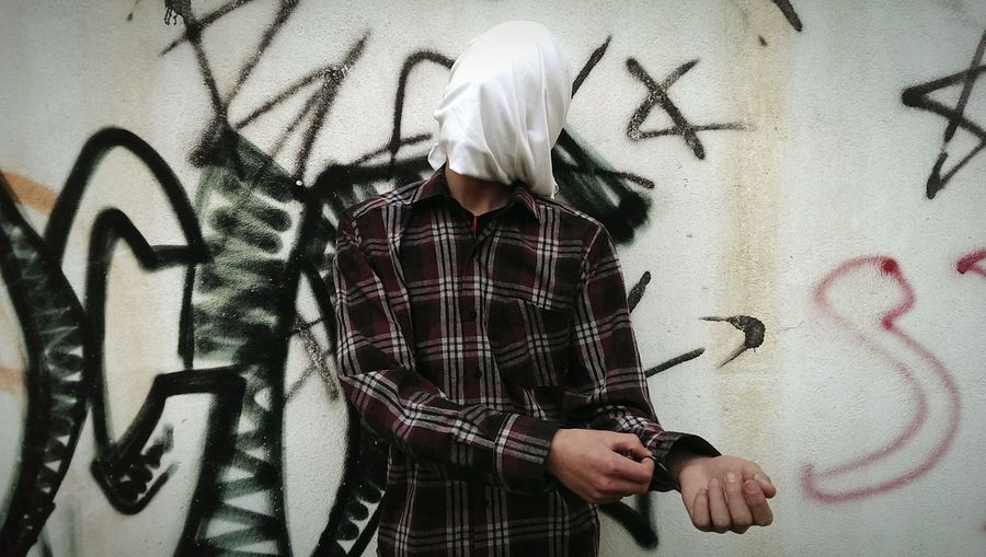 Man with face covered by cloth against graffiti wall