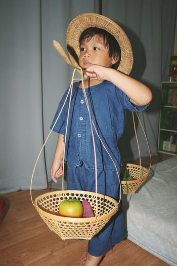 Cute boy carrying fruits in basket while standing on floor at home