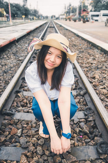 Portrait of woman sitting on railroad track against sky