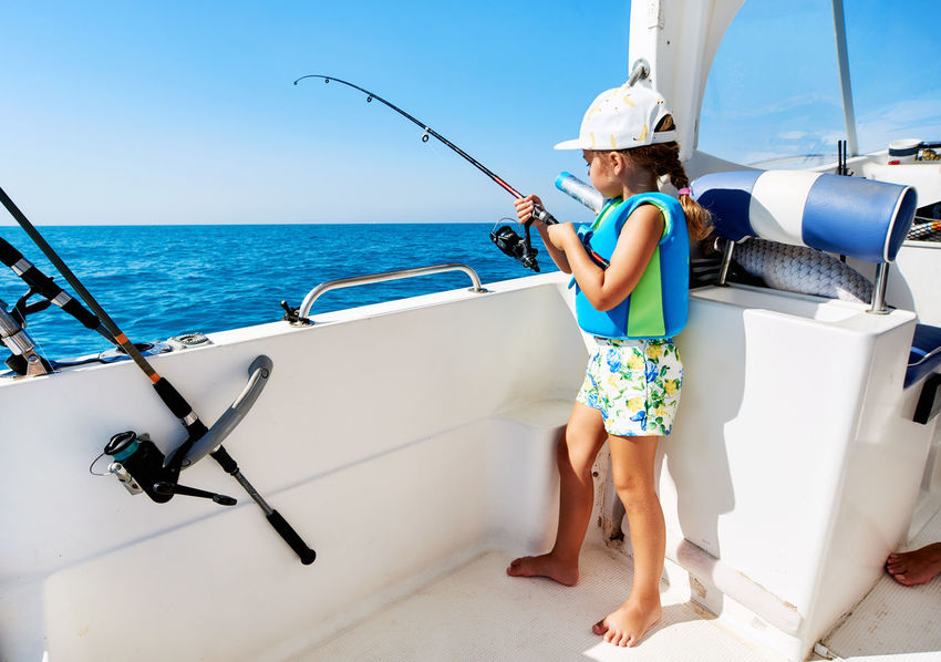 Lovely little girl with a fishing rod fishing on the boat 5 Years Old Beautiful Girl Bright Colors Fishing Rod Recreational Boat Standing Summertime Sunlight Catch Of Fish Fishing Fishing Boat Fishing Time Full Length Hobbies Horizon Over Water Leisure Activity Little Girl Nautical Vessel One Person Real People Recreational Pursuit Sea Summer Sunny Day Water