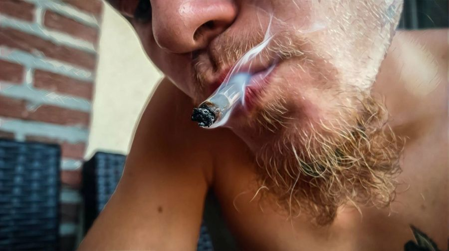 Close-Up Of Man Smoking Marijuana Joint