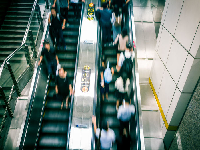 Blurred Motion Of People On Escalator In Subway