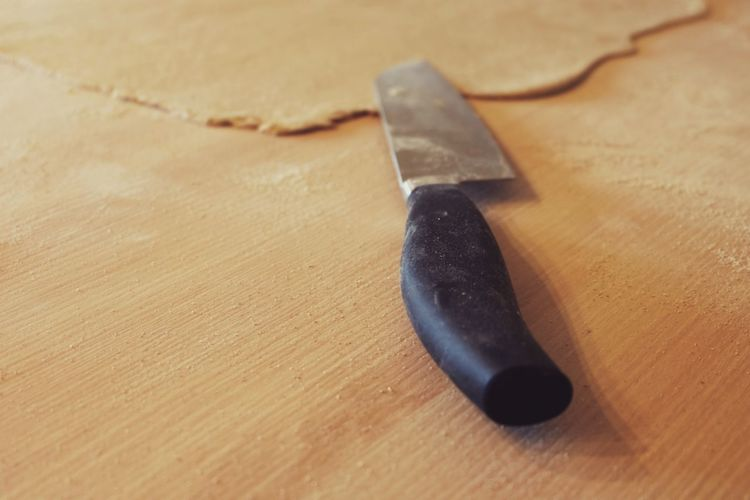 Close-up of kitchen knife by rolled pizza dough on table