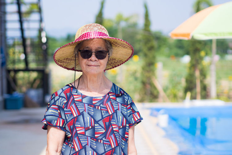 A portrait of an elderly woman wearing sunglasses and straw hat while standing side swimming pool