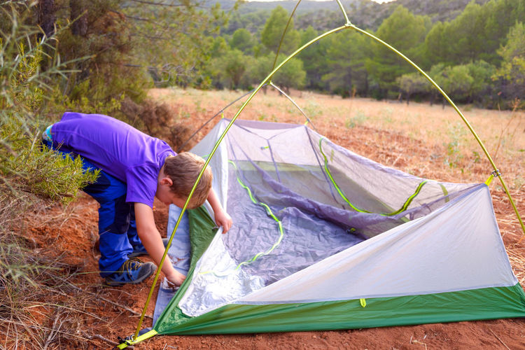 Boy installing tent on land in forest